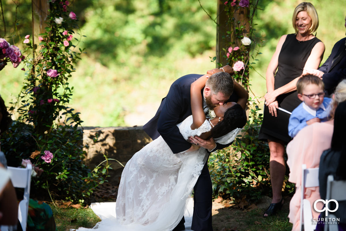Groom dips his bride during the ceremony.