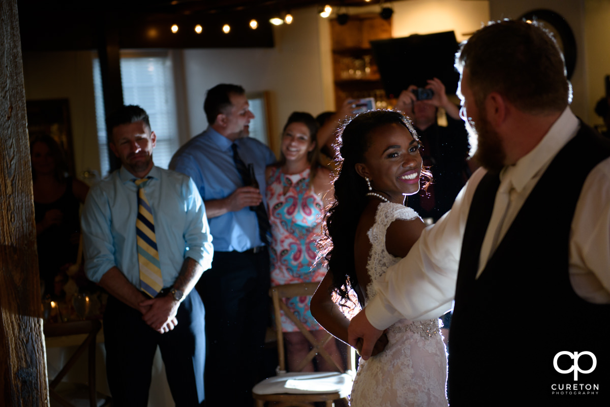 Bride smiling at her groom during their first dance at their Larkin's wedding reception.
