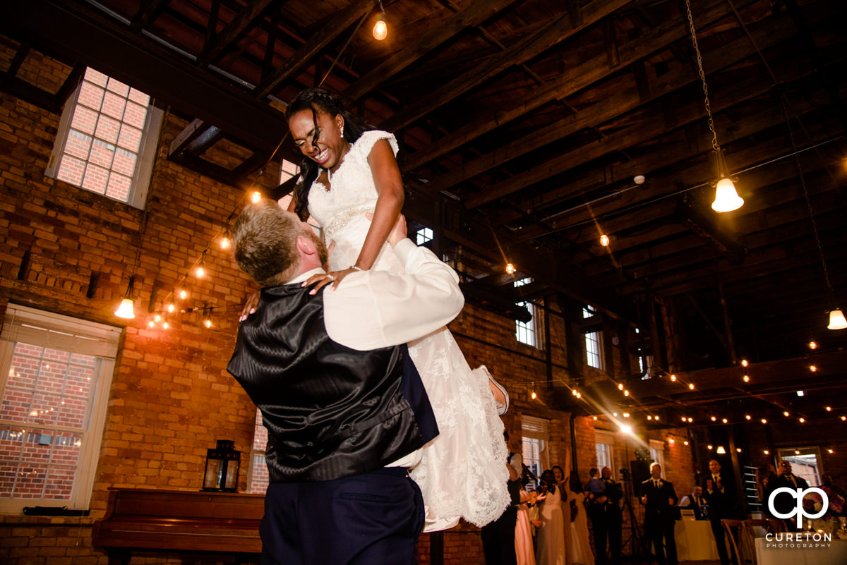 Groom lifting his bride Dirty Dancing style during their first dance at the wedding reception in Greenville.