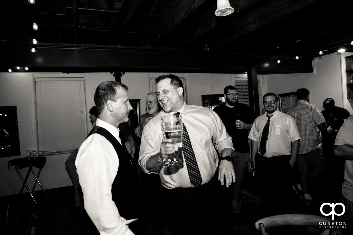 Groomsmen pass around the boot full of beer.
