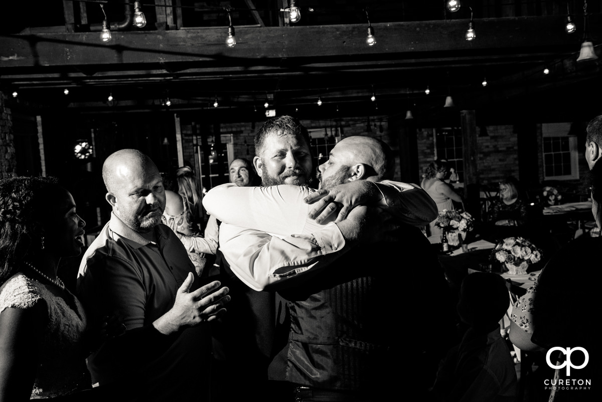 Groomsmen hugging the groom.