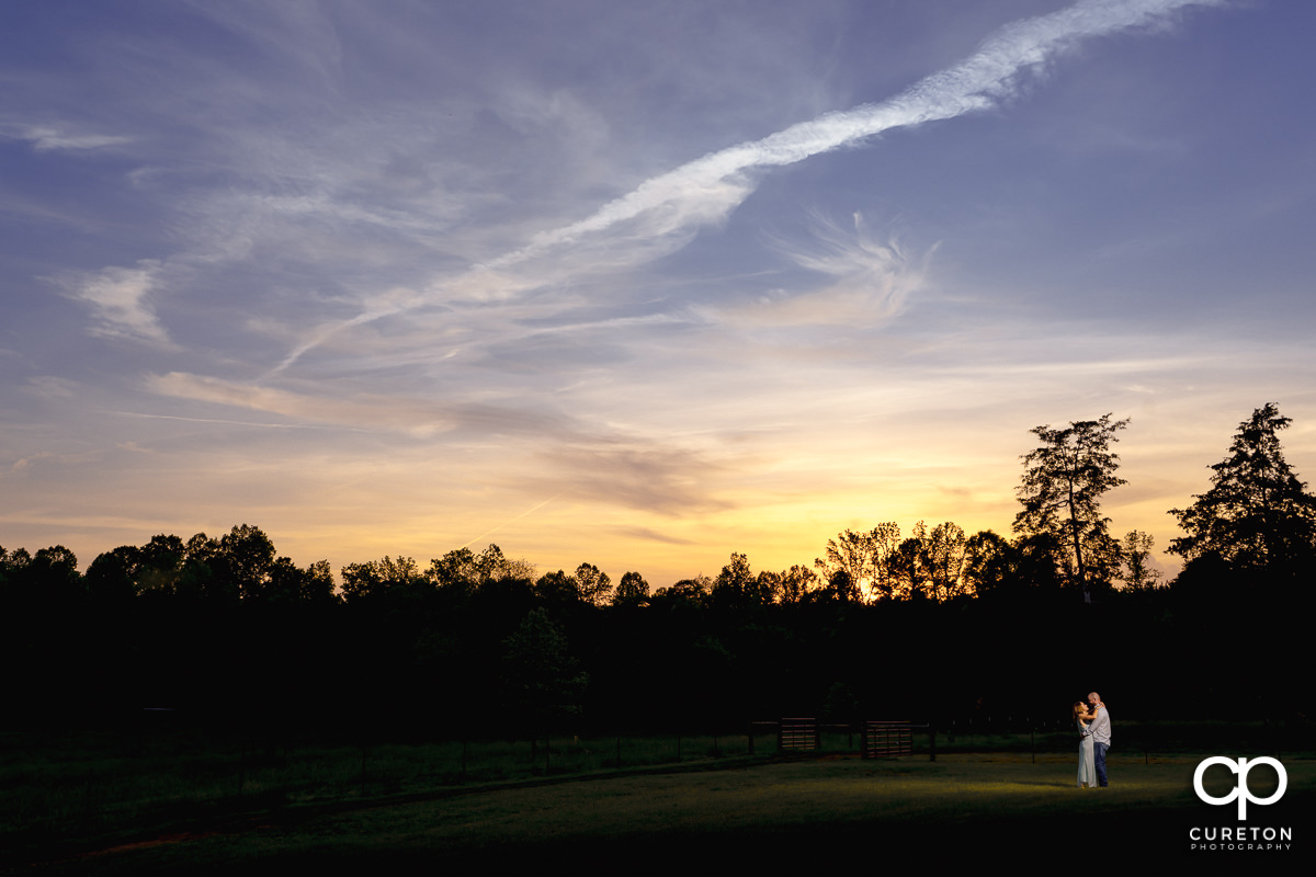 Future bride and groom dancing at sunset in a field during a family farm engagement session in Gray Court,SC.