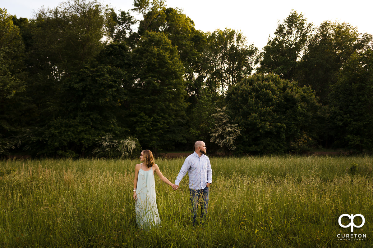 Engaged couple walking though a field of tall grass during a family farm engagement session in Gray Court,SC.