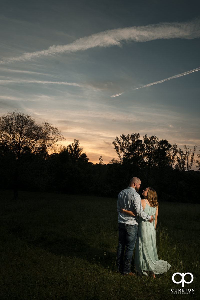 Engaged couple dancing underneath a sunset sky during a family farm engagement session in Gray Court,SC.