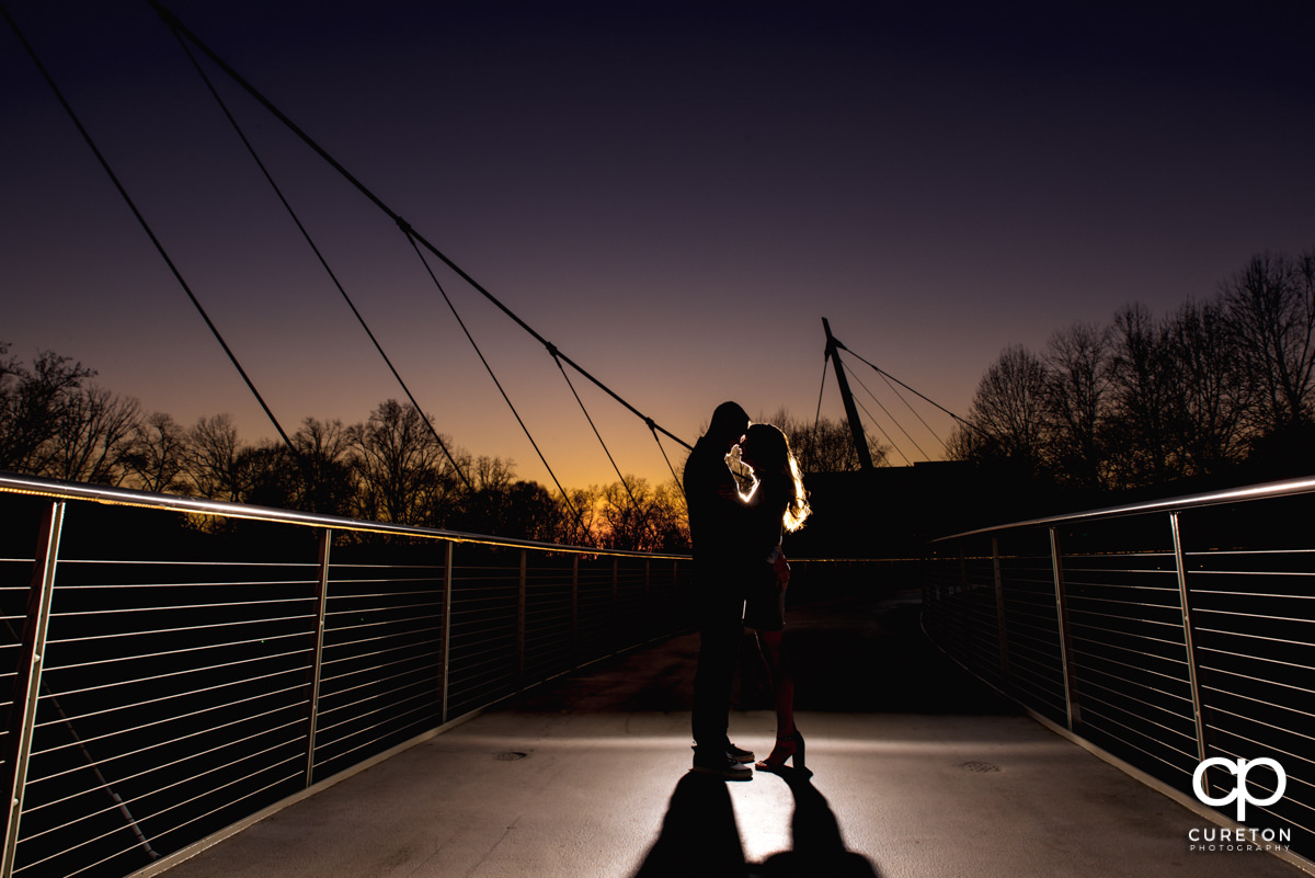 Future bride and groom hugging on the Liberty Bridge at sunset during a Falls Park Engagement session in downtown Greenville,SC.