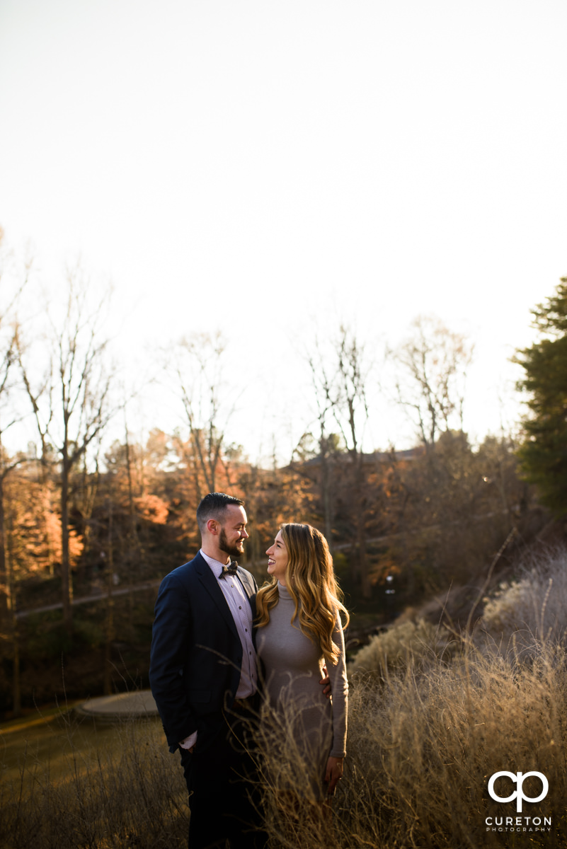 Future husband and wife standing in glowing sunlight during an engagement session in Falls Park in downtown Greenville,SC.