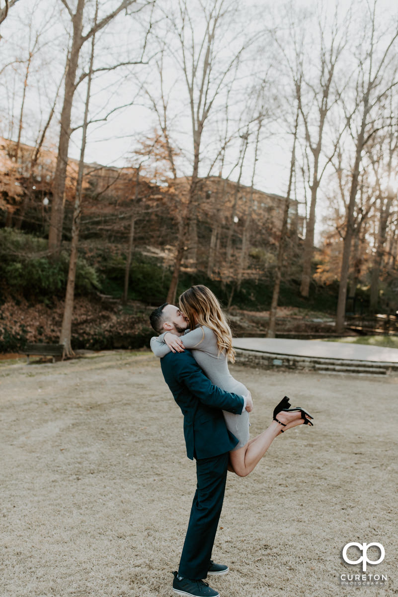 Man lifting his fiancee in the air as she kisses him.