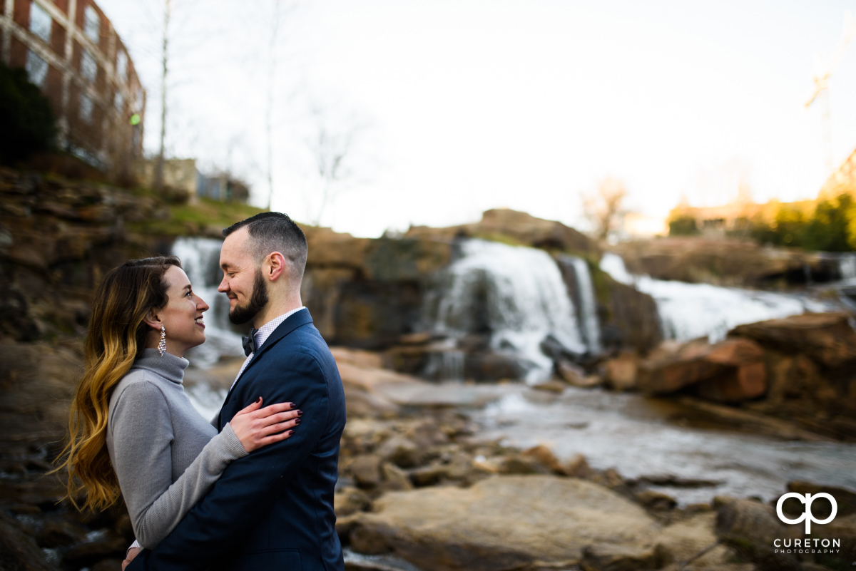 Engaged couple standing in front of the falls in Falls Park in downtown Greenville,SC.
