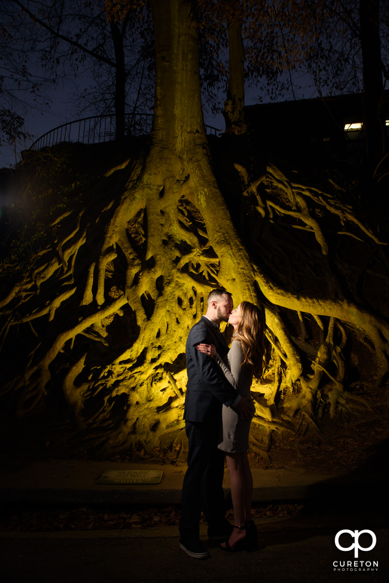 Future bride and groom kissing in front of the landmark tree roots in Falls Park during an engagement session in downtown Greenville,SC.