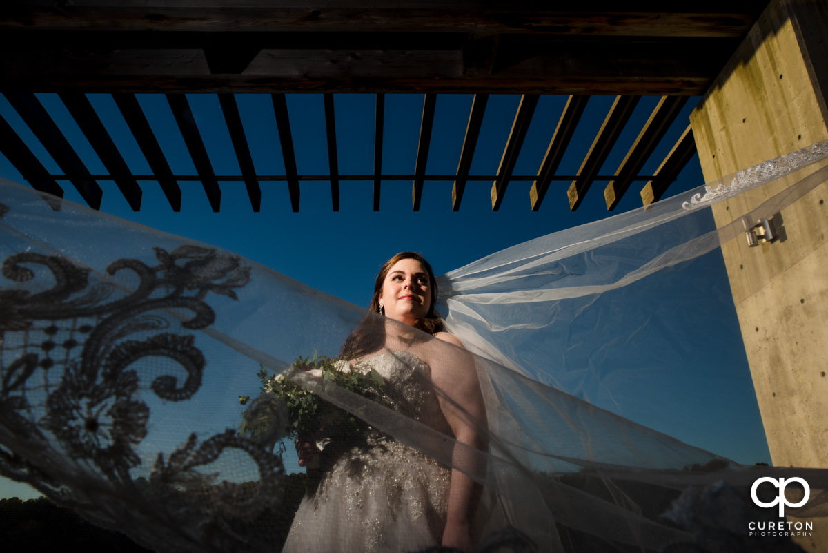 Bride underneath a portico by the lake at Furman University with her veil blowing in the wind.
