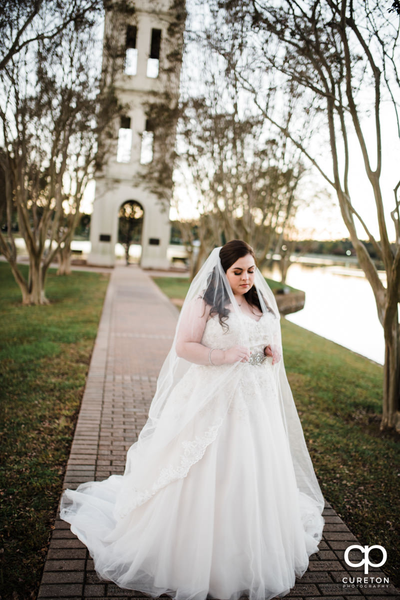 Bride holding onto her long veil in front of the bell tower at Furman during her bridal session.