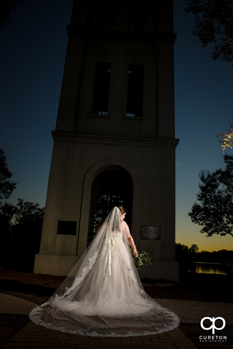Bride showing off her cathedral veil during a sunset bridal session by the bell tower at Furman University.