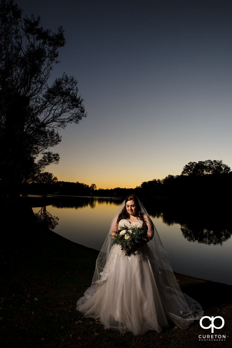 Bride posing by the lake at Furman University during a bridal session.