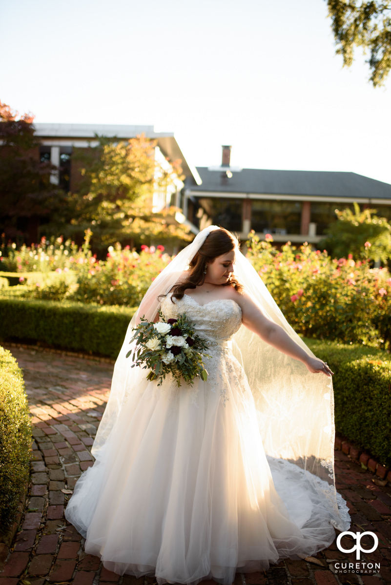 Bride holding out her veil in the sunlight during a bridal session at Furman University.