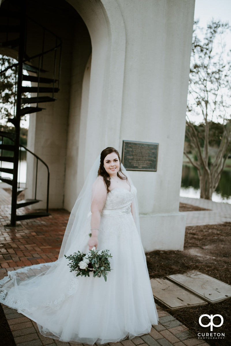 Bride holding her flowers out by the Bell Tower.