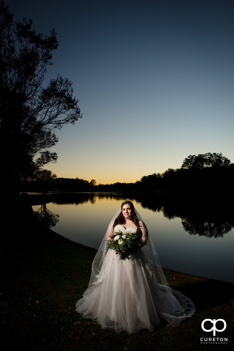 Bride by the lake at sunset.