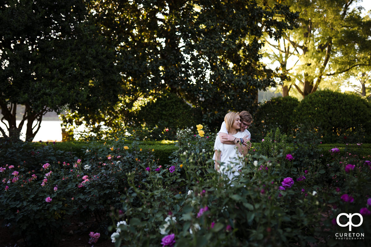 Engaged couple hugging in the rose garden during their college graduation and engagement session at Furman University.