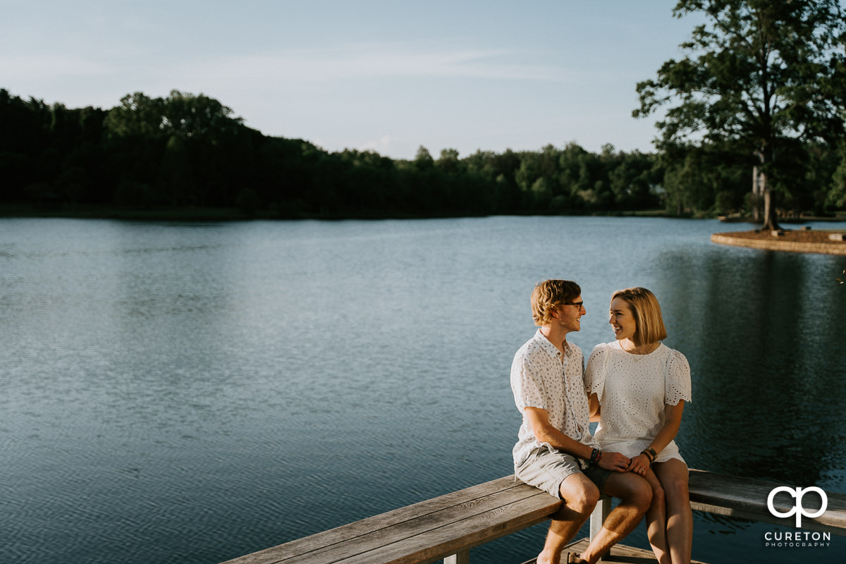 Engaged couple sitting by the lake at Furman .