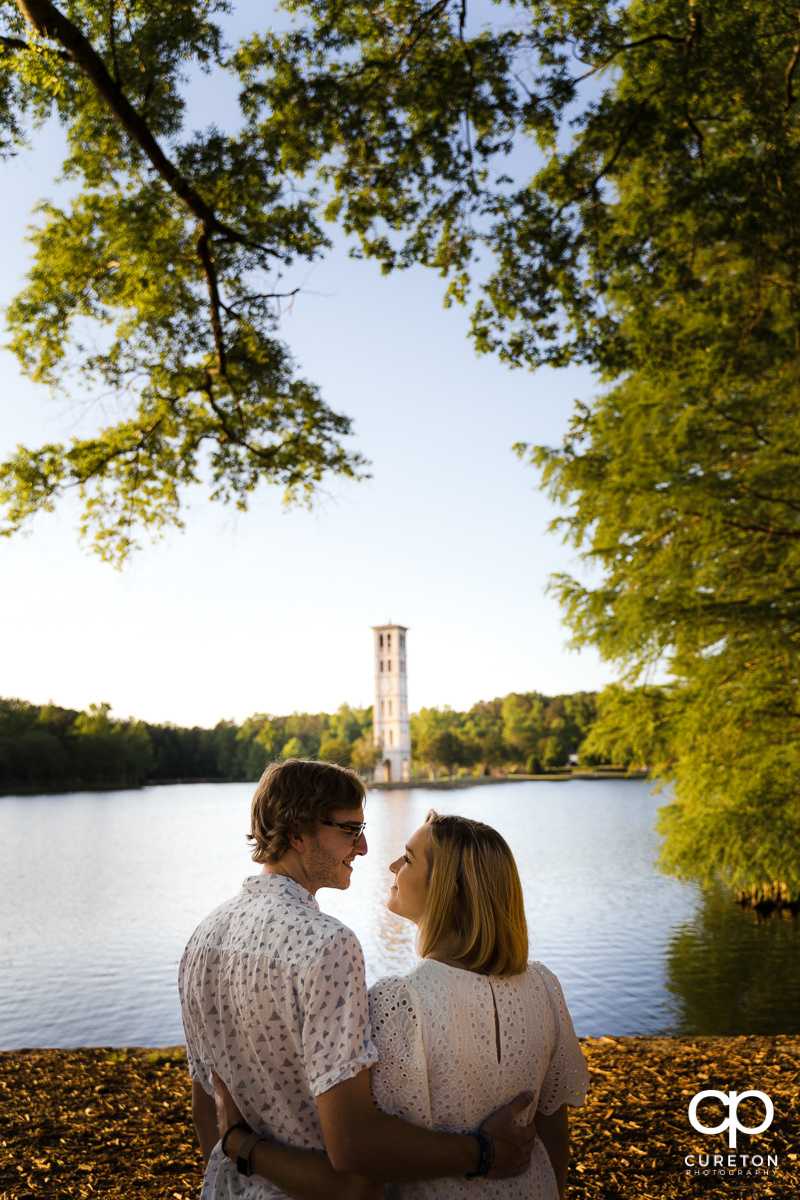 Engaged Furman students looking at each other by the lake with the Bell Tower in the background during their college graduation and engagement session at Furman University.