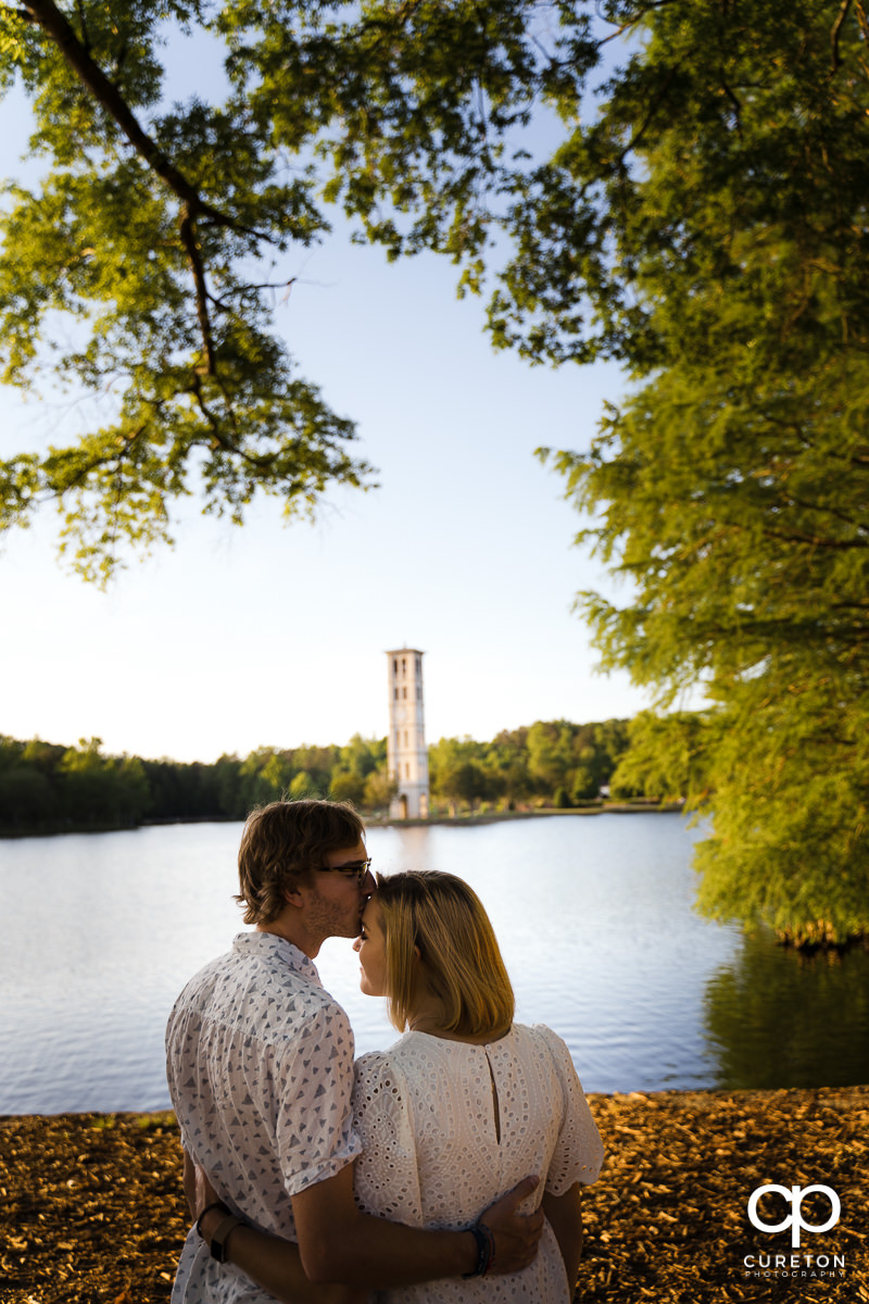 Engaged Furman students kissing each other by the lake with the Bell Tower in the background during their college graduation and engagement session at Furman University.