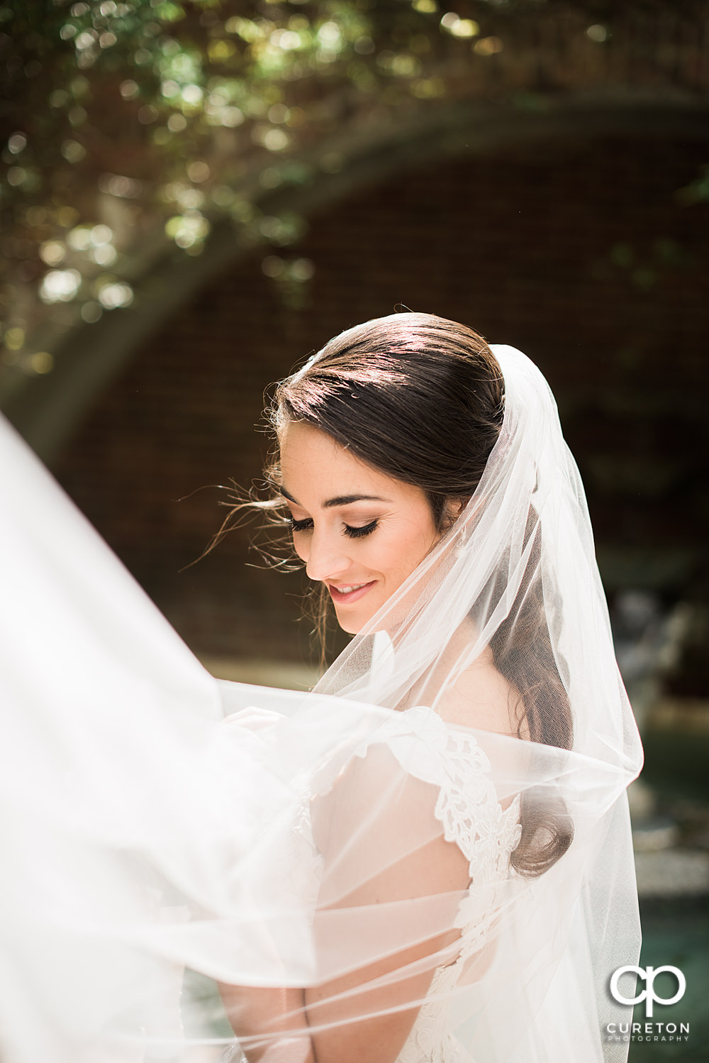 Bride smiling with her veil blowing in the rose garden at Furman.