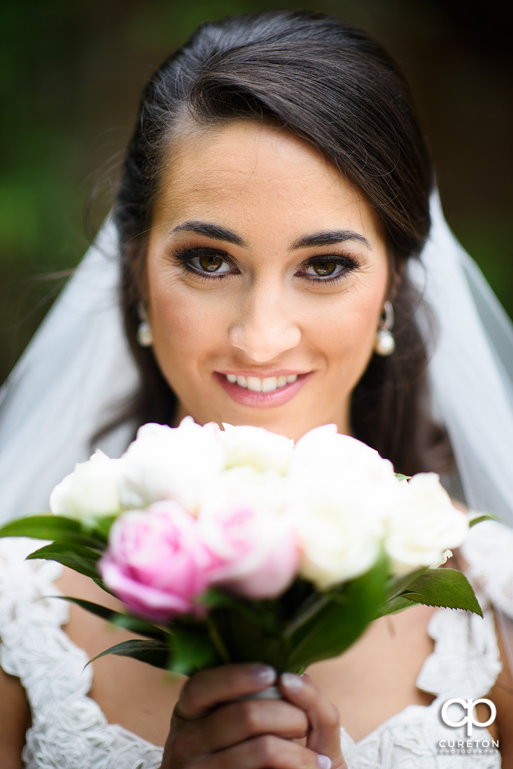 Bride holding her flowers up to her face.