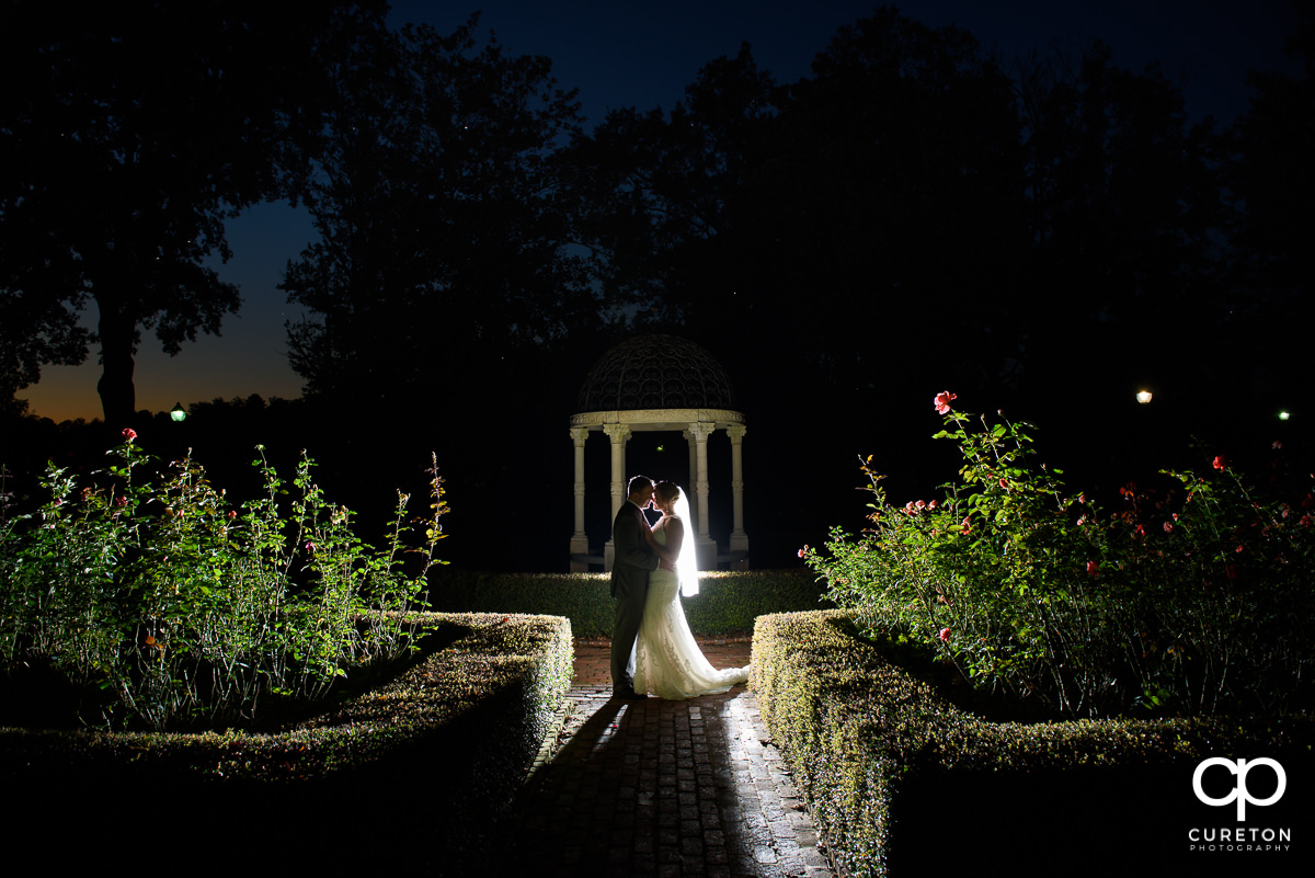 Bride and groom standing in the rose garden at Furman University after their intimate wedding ceremony.
