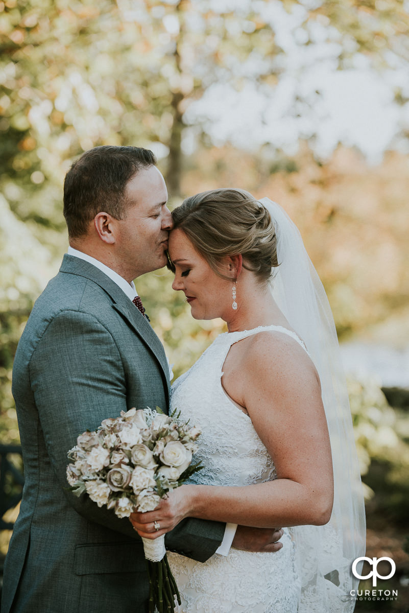 Groom kissing his bride on the forehead after their Furman rose garden wedding.