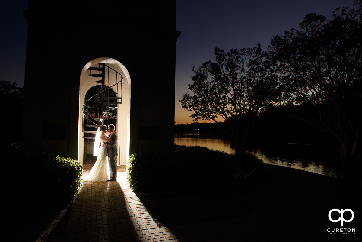 Backlit photo of a bride and groom at sunset in the bell tower at the Furman lake.