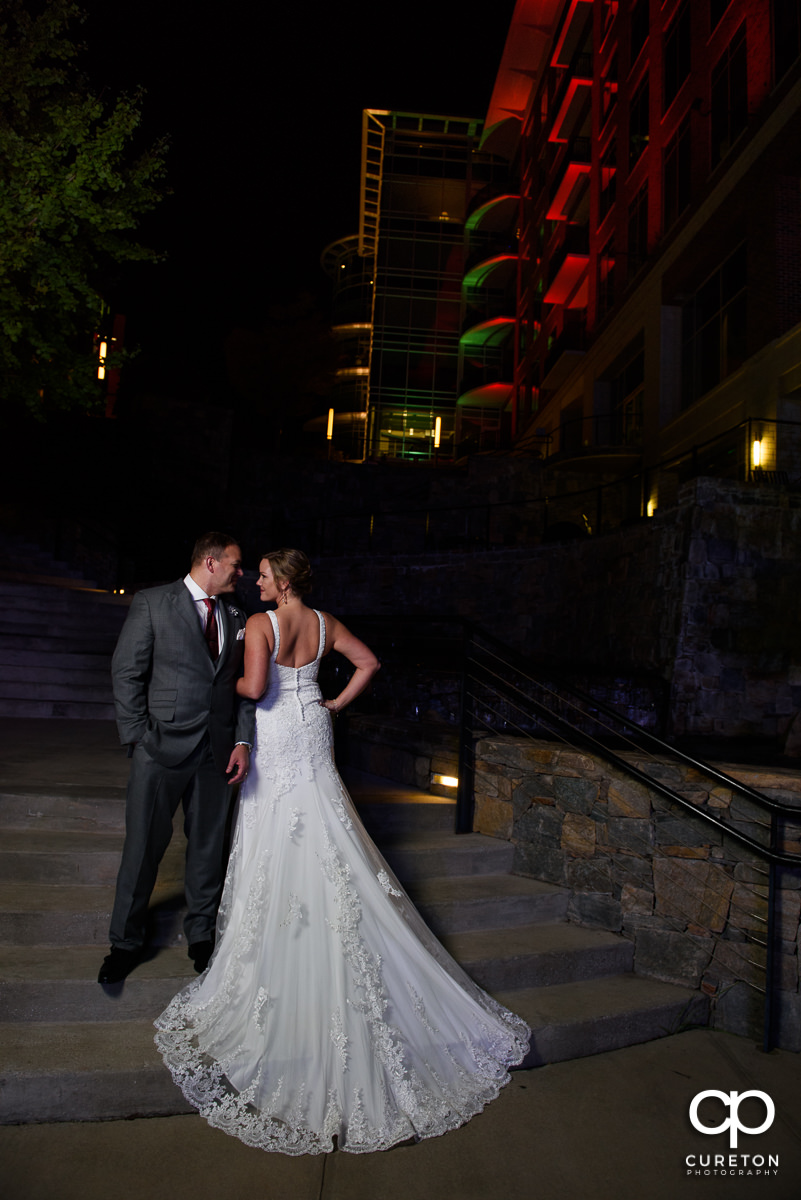 Bride showing the back of her dress with her groom in downtown Greenville.