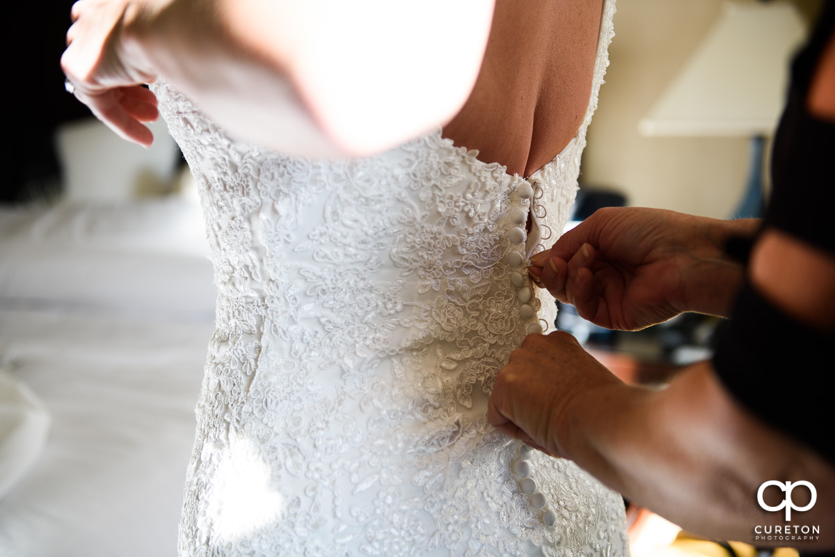 Bride getting the back of her dress zipped up.