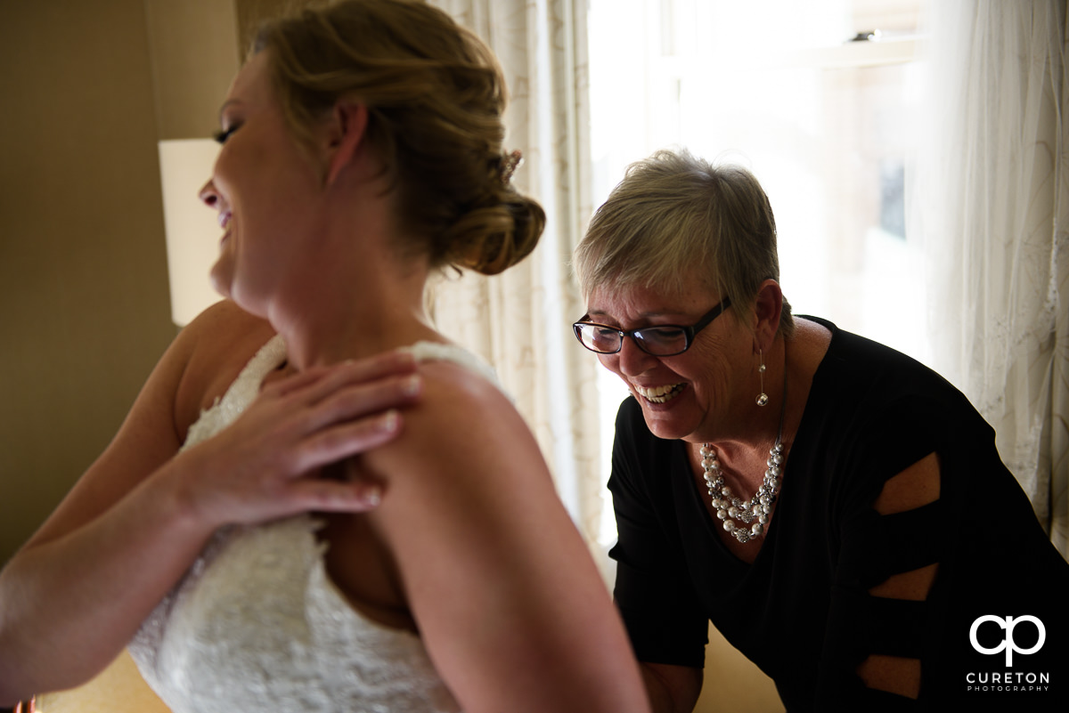Bride's mother helping her in to the dress.