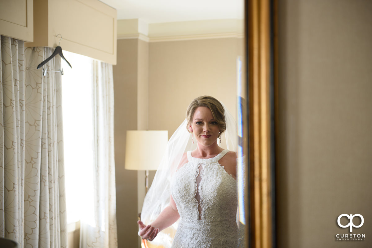 Bride looking at herself in the mirror at the Westin Poinsett Hotel.