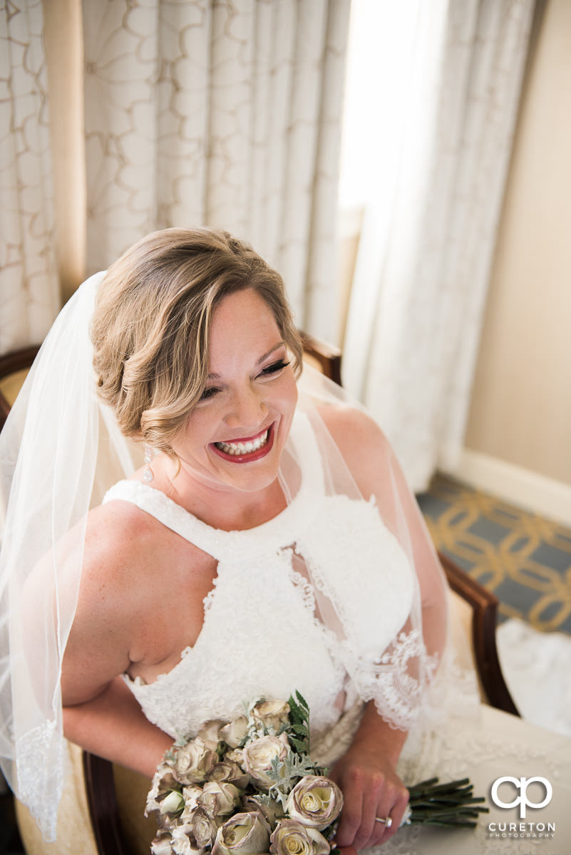 Bride smiling holding her bouquet.