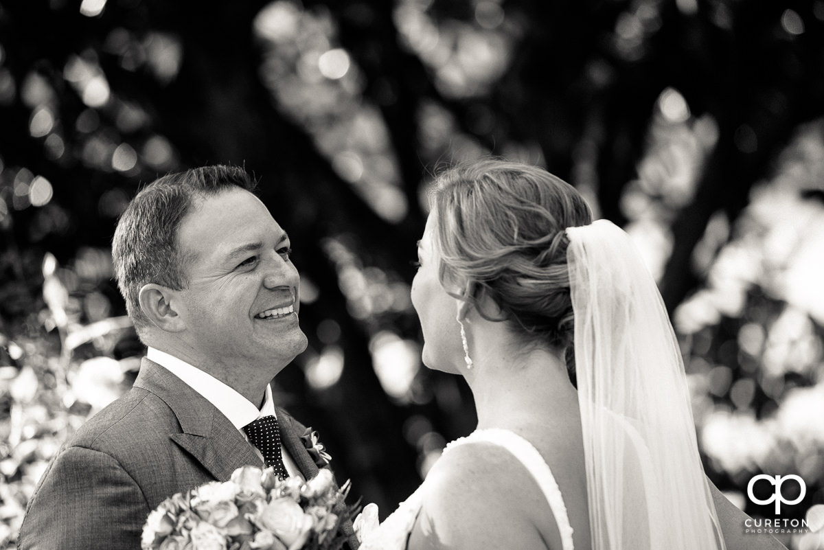 Groom smiling when he sees his bride for the first time in her dress.
