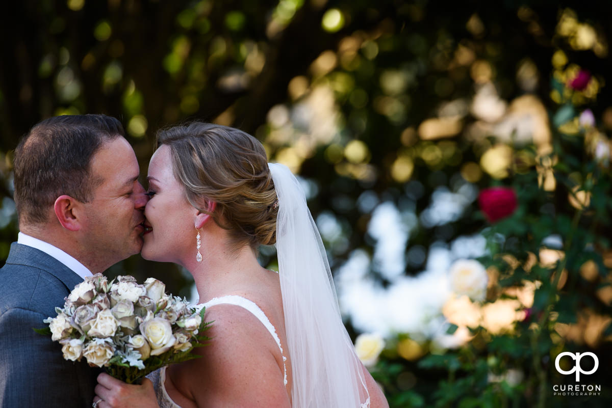 Bride and groom kissing in the rose garden.