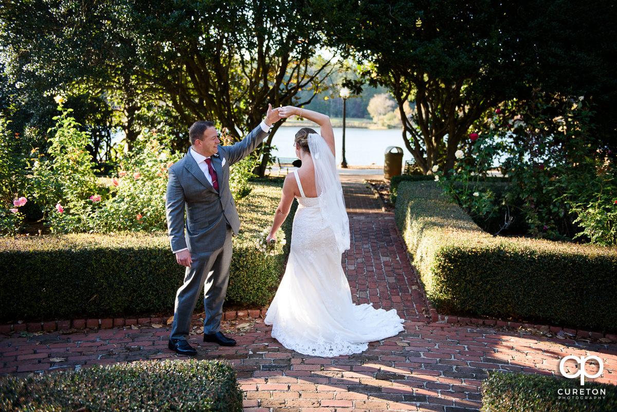 Groom twirling his bride around.