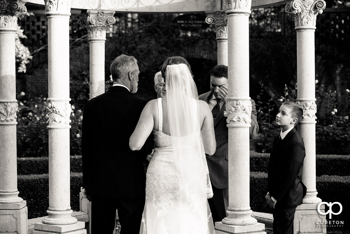 Groom wiping a tear from his eye as he sees his bride walking down the aisle.