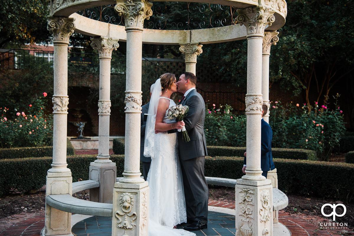 FIrst kiss at the rose garden wedding.