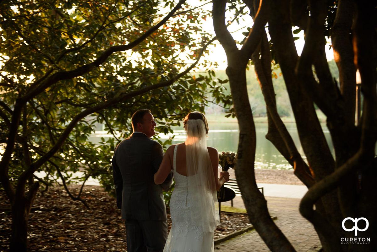 Newlywed bride and groom walking toward the lake at Furman.