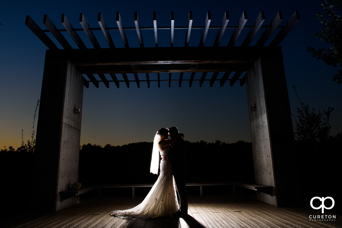 Bride and groom silhouette by the lake at Furman.