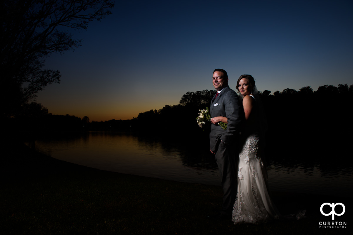 Bride and groom standing by the lake at Furman after their wedding.
