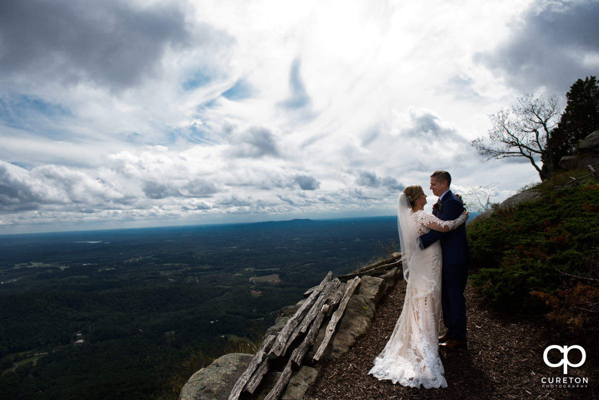 Bride and groom hugging on a mountaintop after their Glassy Chapel wedding.
