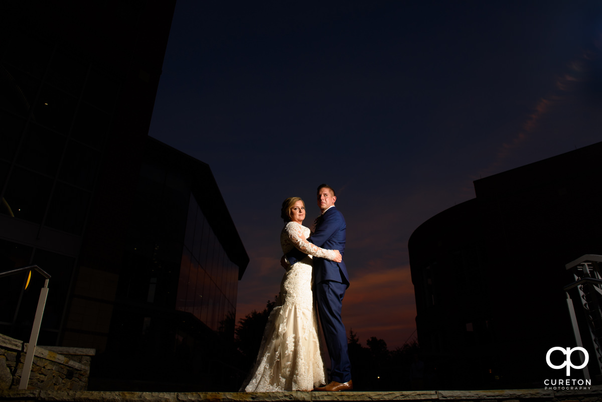 Bride and groom standing at the top of the steps an sunset during their wedding reception at Larkin's Cabaret Room.