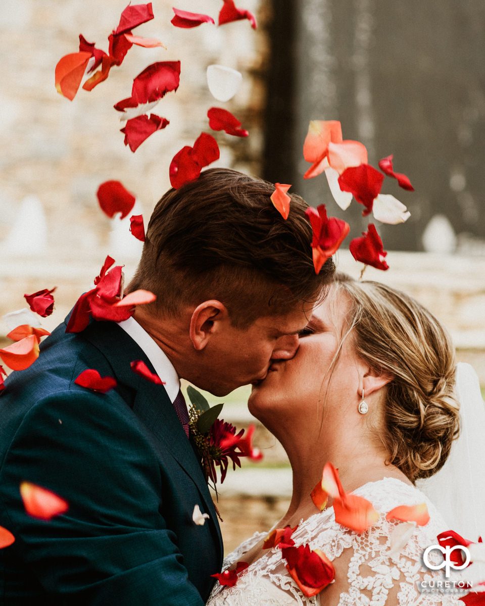 Bride and groom kissing as flower pedals fall around them on their wedding day in downtown Greenville,SC.