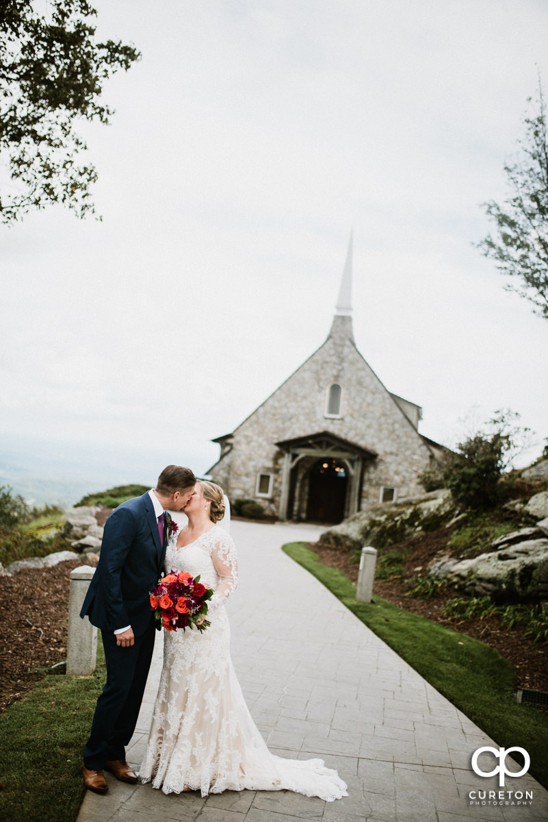Bride and groom kissing with Glassy Chapel in the background.