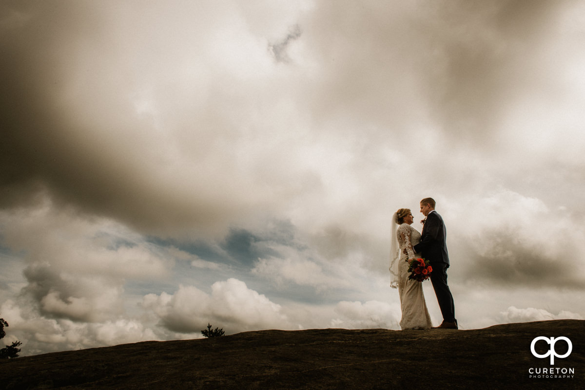 Bride and groom on top of the rock at Glassy Chapel after their wedding ceremony.