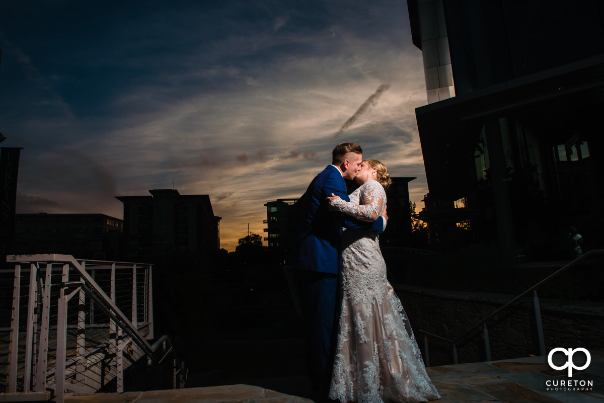 Groom kissing his bride in downtown Greenville at sunset at their wedding reception at Larkin's Cabaret Room in Greenville,SC.