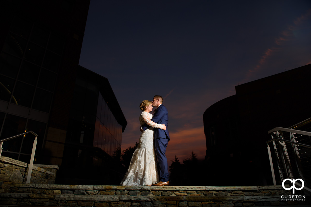 Groom kissing his bride on the forehead at sunset during their Larkin's Cabaret Room wedding reception in downtown Greenville,SC.