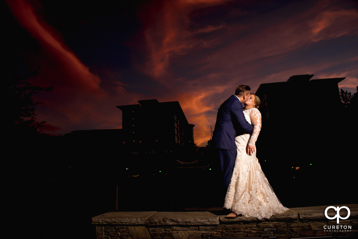 Bride and groom kissing at sunset in downtown Greenville,SC at their wedding reception at Larkin's Cabaret Room.